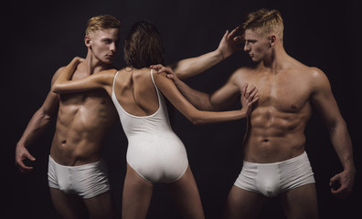 Sport people or team work. Circus gymnasts at pilates or yoga training. Fitness and dieting. Flexibility in acrobatics. Gymnastic school and energy. Twins men with muscular body and girl coach.