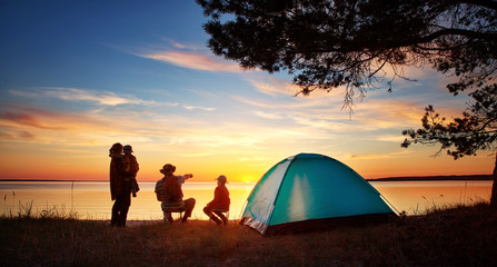 Rodzinny odpoczywać z namiotem w naturze przy zmierzchem
