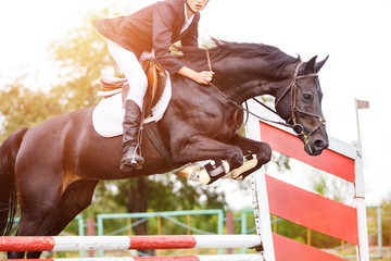 Young rider man jumping on horse over obstacle on show jumping competition