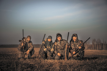 Men hunters group team portrait in rural field posing together against sunrise sky during hunting season. Concept for teamwork  friendship and brotherhood.