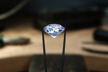 Beautiful diamond stone in tongs. Craft jewelery making with professional tools in jeweller studio. Macro shot.
