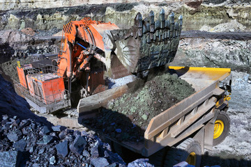 Large quarry dump truck. Loading the rock in the dumper. Loading coal into body work truck.