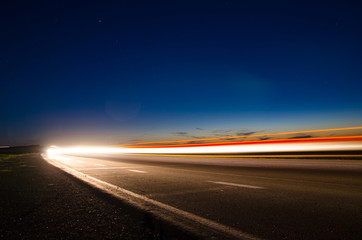 The asphalt road in the countryside with the light passing through it at the speed of cars on long exposure