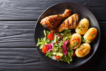 Delicious food: grilled chicken drumsticks with new potatoes and fresh salad closeup on a plate. horizontal top view