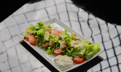 Caesar salad on a white plate and a glass background