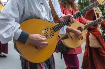 Men in medieval costume plays mandolin during festival