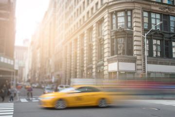 Żółta taksówka w Nowym Jorku pędząca ulicą Manhattan