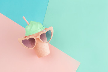 Fancy glass with heart shape sunglasses on pastel colors background, Summer concept