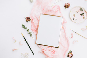 Creative wedding composition with photo frame mock up, pink blanket, flowers, eucalyptus branches and brushes on white background. Flat lay, top view stylish art concept.