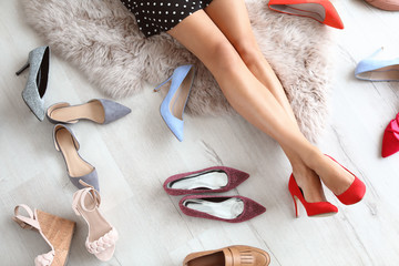Young woman choosing shoes on floor