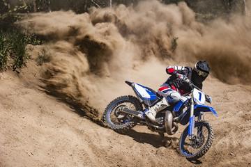 Jeździec Motocross tworzy dużą chmurę pyłu i gruzu