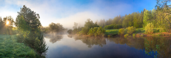 wiejska panorama z rzeką, mgłą i lasem o wschodzie słońca