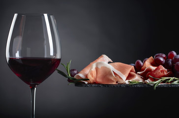 Prosciutto with rosemary and glass of red wine.