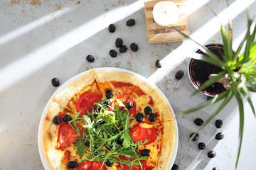 Pizza z pomidorami, czarnymi oliwkami, rukolą.
