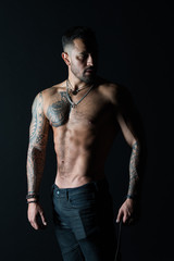 Tattoo model with sexy belly. Man with tattooed arm and chest. Bearded man with strong torso. Sportsman or athlete in fashion jeans. Bodycare with fitness and sport
