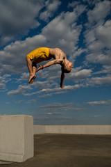 Tricking on street. Martial arts and elements of parkour. Man flips back barefoot. Shooted from bottom foreshortening against sky.
