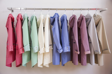 Colorful softshell coats on rack with hangers. Fashion conception.