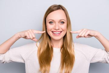 Portret radosna zadowolona dziewczyna gestykuluje jej promieniejących białych zdrowych zęby z dwa palcami wskazującymi patrzeje kamerę odizolowywającą na szarym tle. Koncepcja ortodontyczna