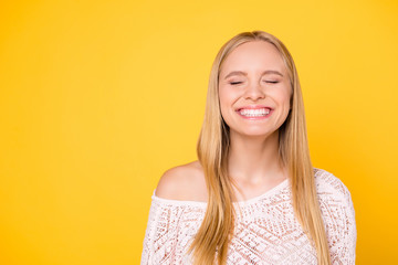 Portrait with copy space empty place of comic funky girl laughing with clenched teeth keeping eyes closed isolated on yellow background
