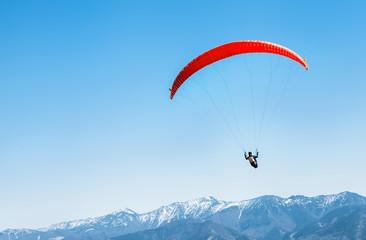 Sportowiec na czerwonej paralotni szybującej nad zaśnieżonymi szczytami górskimi
