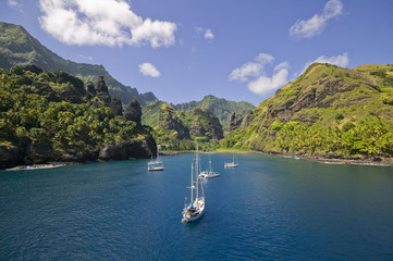 Sailing yachts anchoring in the Bay of Vergins, Marquesas Islands, French Polynesia