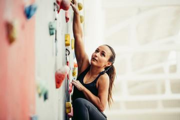 Przycięty widok sprawnej kobiety biznesu, wspinającej się na sztucznej skale w fitness, osiągającej nowe wyżyny w biznesie i sporcie. białe tło z miejsca kopiowania