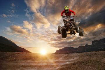 Mężczyzna na atv skacze na szlaku podczas zachodu słońca.