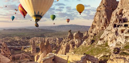 Balony nad tureckim parkiem narodowym w Göreme. Panorama Kapadocji - wielobarwne balony latające nad górską doliną starożytnego miasta jaskiniowego Uchisar.