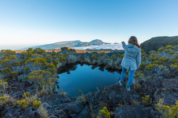 Girl pointing the Piton des Neiges over a lake in Reunion Island