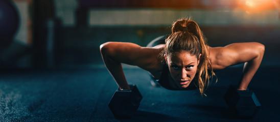 Trening obwodowy. Młoda kobieta ćwiczy przy gym