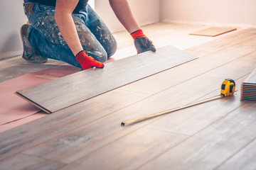 Worker professionally installs floor boards