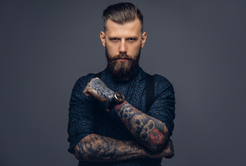Handsome old-fashioned hipster in shirt and suspenders, pose with crossed arms. Isolated on a dark background.