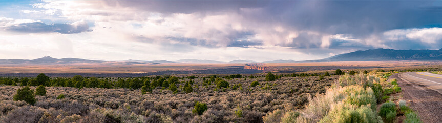 Rio Grande Gorge at Sunset with Dramatic Cloudscape and Taos Mountains in the Background.