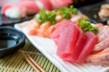 Mixed sliced fish sashimi in white plate. Sashimi Salmon and Tuna set with Tuna, flying fish roe caviar and Foie Gras closeup. Japan restaurant menu