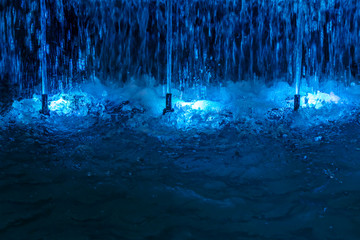 fountain with blue illuminations at night. colored water jets closeup view