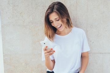 junge frau lacht und schaut auf ihr smartphone