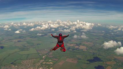 Spadochroniarz w czerwonym kombinezonie swobodnie spadającym ponad chmurami