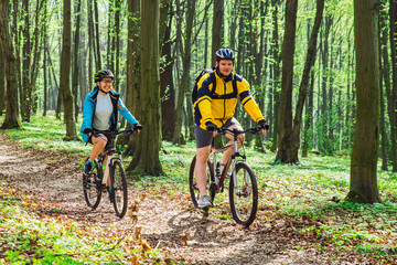 couple riding bicycle in forest in warm day