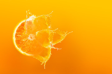 Fresh half slice of ripe orange fruit floation with splash drop on orange juice with copy space
