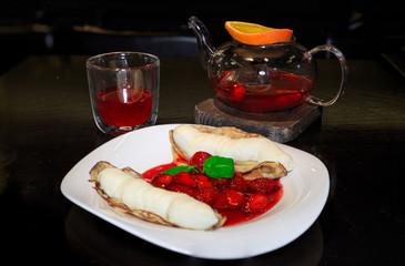 Блинчики с мороженым, засыпанные клубникой и мятой, чайник с фруктовым чаем и бокал