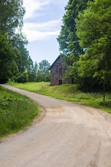 An old stone house near the country road through the green forest on a clear sunny day, Latvia