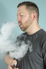 Young man vaping smoking an e-cigarette