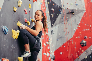 Professional sportwoman climber moving up on steep rock, climbing on artificial wall indoors, side view. Extreme sports and bouldering concept.
