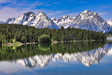 The Grand Tetons of Wyoming are reflected perfectly in the still waters of Jackson Lake
