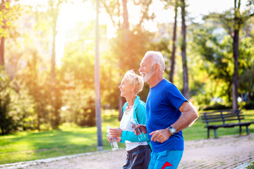 Happy senior couple jogging outdoors in park.
