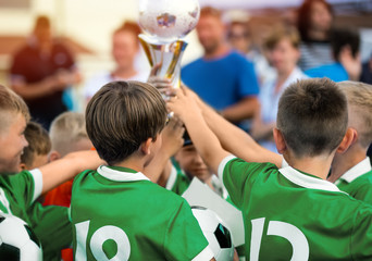 Kids Raising Golden Cup for Winning Sports Team. Children in Green Sportswear Celebrating Sport Success. Happy Kids Celebrate the Victory