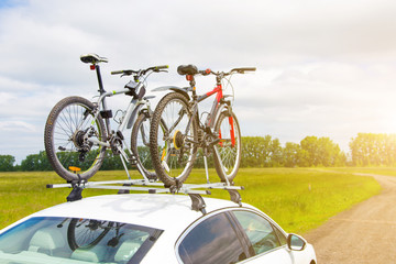 Bike transportation - two bikes on the roof of a car against a beautiful sky. the end of the transportation of large loads and travel by car