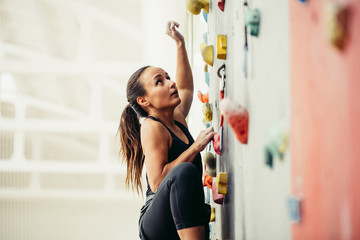 Side view of professional climber female at the rock climbing wall at the gym. Light background with copyspace
