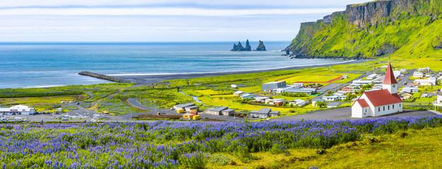 Widok bazaltowe stosy Reynisdrangar, czarna piasek plaża, kościół i miasto Vik, Iceland