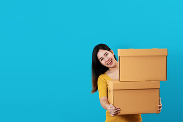 Portrait of young asian entrepreneur happy smiling and holding or carrying pile of boxes in hands with blue isolated background and copy space. Asian woman move to new home or ecommerce owner concept.